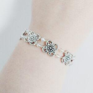 Armband bloemen swarovski kristal. Armband met metalen bloemen met er tussen kleine swarovski kraaltjes in de kleur crystal (kristal). Er zit een metalen kraal bij het slotje.De armband wordt getoond om de pols van een blanke vrouw.