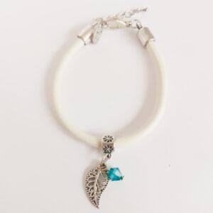 Armband wit leer swarovski groen blauw. Wit leren armband met een metalen bedeltje in de vorm van een blaadje met een swarovski kraal in de kleur blue zirkon (groen blauw).