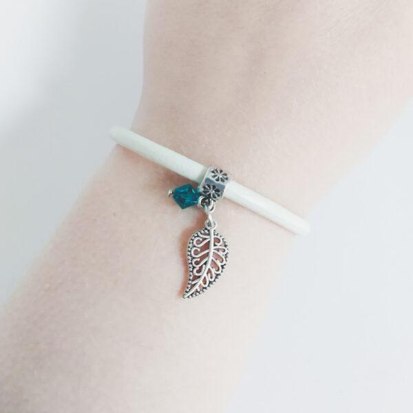 Armband wit leer swarovski groen blauw. Wit leren armband met een metalen bedeltje in de vorm van een blaadje met een swarovski kraal in de kleur blue zirkon (groen blauw). De armband wordt getoond om de pols van een blanke vrouw.