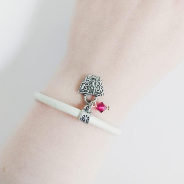 Armband wit leer swarovski donker roze. Wit leren armband met een metalen bedeltje in de vorm van een tasje met een swarovski kraal in de kleur fuchsia (donker roze). De armband wordt getoond om de pols van een blanke vrouw.