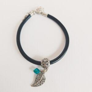Armband zwart leer swarovski blauw groen. Zwart leren armband met een metalen bedeltje in de vorm van een blaadje met een swarovski kraal in de kleur blue zirkon (blauw groen).