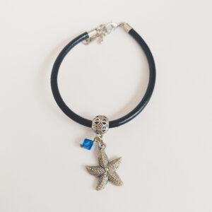 Armband zwart leer swarovski donker blauw. Zwart leren armband met een metalen bedeltje in de vorm van een zeester met een swarovski kraal in de kleur capri blue (donker blauw).