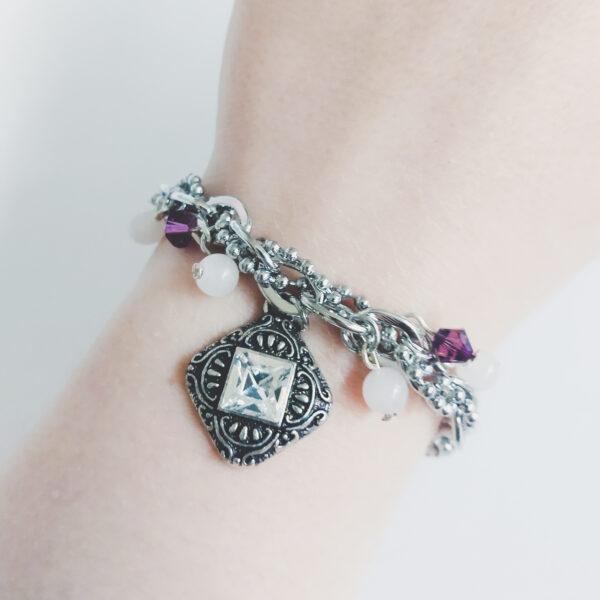 """Armband schakels swarovski paars. Armband met metalen schakels met een bolletjesketting erdoorheen geregen. Er hangen kraaltjes aan, 2 amethyst (paarse) swarovski kraaltjes en 4 witte agaat kraaltjes. Er hangt ook een vierkante metalen hanger met een vierkante swarovski steen in een kristal kleur. Met een metalen bedeltje bij het slotje met de tekst """"Love"""" erop. De armband wordt getoond om de pols van een blanke vrouw."""