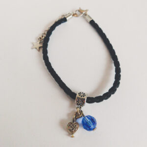Armband leer swarovski donker blauw. Armbandje van gevlochten zwart leer met een bedeltje van een hartje met een oneindige knoop erop met daarnaast een 8 mm swarovski kraal in de kleur sapphire (donker blauw).