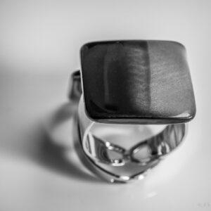 Verstelbare ring met een parelmoer steen met strepen in de kleuren zwart en grijs.