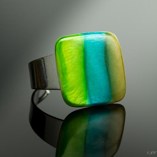 Verstelbare ring met een parelmoer steen met strepen in de kleuren groen, blauw-groen en bruin.