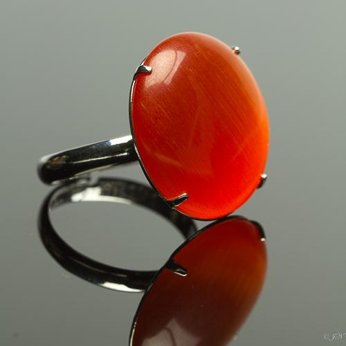 Metalen verstelbare ring met cateye steen in de kleur oranje rood.