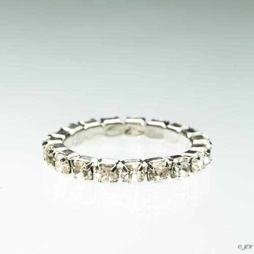 Metalen ring met kleine strass steentjes rondom in de kleur kristal. De ring is niet verstelbaar en heeft een binnemaat van 18 mm.