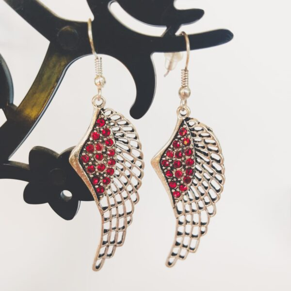 Oorbellen met een wing (vleugelvormige hanger) met swarovski steentjes in de kleurlight siam, donker rood.