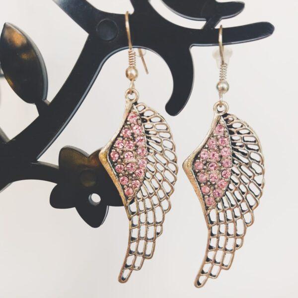 Oorbellen met een wing (vleugelvormige hanger) met swarovski steentjes in de kleurlight rose, licht roze.