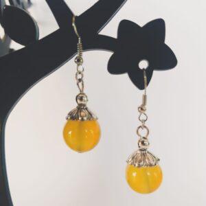 Oorbellen met een grote agaat kraal in de kleur geel, met een gedecoreerd metalen kapje er bovenop.