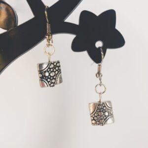Oorbellen met een vierkante metalen hanger met kleine cirkels erop.