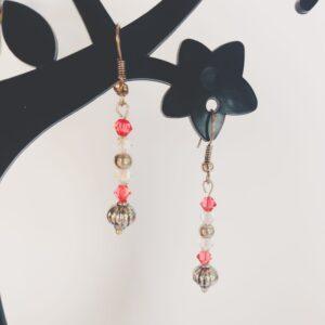Oorbellen met kleine swarovski kraaltjes in de kleur padparadscha (een roze-oranje kleur) en crystal moonlight, daaronder hangt een metalen gedecoreerde kraal.