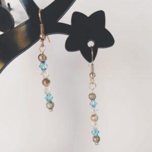 Oorbellen met kleine swarovski kraaltjes in de kleur aquamarine (een licht blauwe kleur) en crystal moonlight (doorzichtig met gelige glans), daartussen hangen metalen kraaltjes met een beetje textuur..