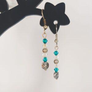 Oorbellen met kleine swarovski kraaltjes in de kleur blue zirkon (een blauw-groene kleur) en crystal moonlight (doorizchtig met gelige glans), daaronder hangt een metalen gedecoreerde kraal met golven.