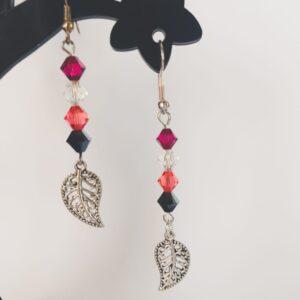 Oorbellen met swarovski kralen in de kleuren fuchsia (donker roze), padparadscha (roze-oranje), crystal en jet hematite (zwart). Met daaronder een metalen bedeltje in de vorm van een blaadje.