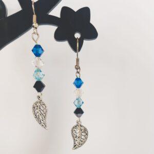 Oorbellen met swarovski kralen in de kleuren capri blue (donker blauw), aquamarine (licht blauw), crystal en jet hematite (zwart). Met daaronder een metalen bedeltje in de vorm van een blaadje.