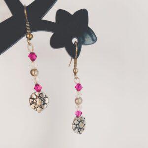 Oorbellen met kleine swarovski kraaltjes in de kleuren fuchsia (donker roze) en crystal moonlight (doorzichtig met een gelige glans), met in het midden een simpele metalen kraal en onderop een gedecoreerde metalen kraal met hartjes erop.
