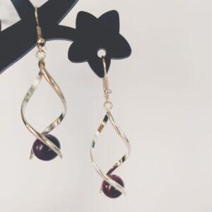 Oorbellen met een silver-plated wikkel met een cateye kraal in de kleur donker paars.