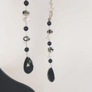 Lange oorbellen met een druppelvormige swarovski hanger in de kleur jet (zwart) met daarboven swarovski kralen in de kleur crystal silver shade (grijs-zilver) en crystal, en parels in black, een zwarte kleur. De oorbel wordt getoond in het oor van een blanke vrouw met blond haar.