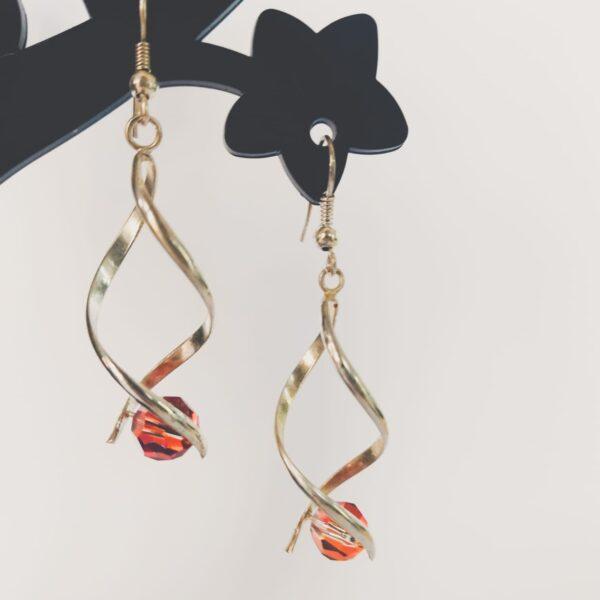 Oorbellen met silver-plated wikkel met een swarovski kraal in de kleur red magma, een rood-oranje kleur.