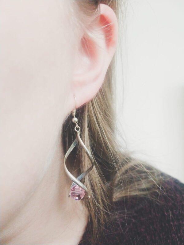 Oorbellen met silver-plated wikkel met een swarovski kraal in de kleur light rose, een licht roze kleur. De oorbel wordt getoond in het oor van een blanke vrouw met blond haar.