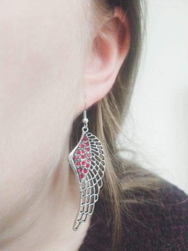 Oorbelen met een wing (vleugelvormige hanger) met swarovski steentjes in de kleur siam, donker rood. Op de foto is een de oorbel in het oor van een blanke vrouw met blond haar.