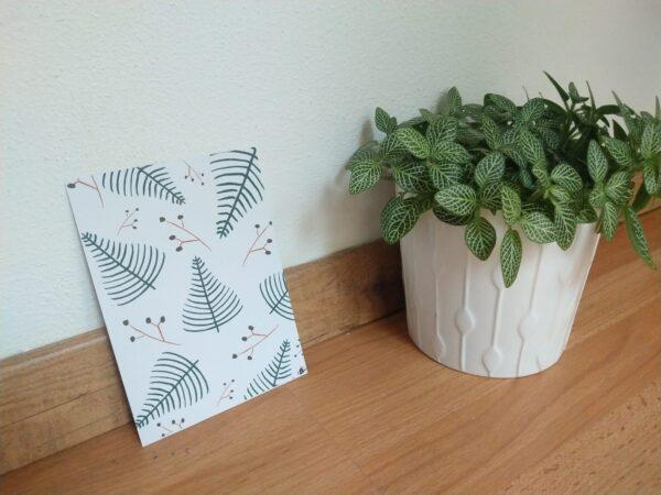 Ansichtkaart met hangemaakte illustraties van kerstboompjes en takjes met rode besjes. Een ansichtkaart met handgemaakte illustraties van een ijsvogel. Op de foto is de kaart tegen een muur te zien met een plantje ernaast.