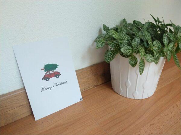 """Een ansichtkaart met handgemaakte illustratie van een rood autootje met een kerstboom op het dak met de tekst """"Merry Christmas"""" eronder. Op de foto is de kaart tegen een muur te zien met een plantje ernaast."""