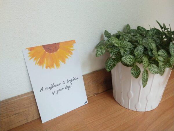"""Ansichtkaart met de tekst """"A sunflower to brighten up your day!"""" en hangemaakte illustraties van een zonnebloem. Op de foto is het kaartje te zien tegen een muur aan met een plantje ernaast."""