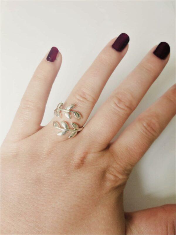 Metalen ring met kleine blaadjes. De ring is verstelbaar. Op de foto is de ring te zien om de ringvinger van een blanke vrouw met bordeaux rode nagellak.