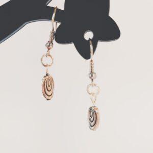 Oorbellen met een ovale metalen hanger met kleine ovalen erop.