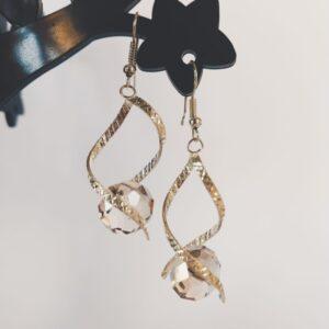 Oorbellen met een metalen helix gedecoreerd met streepjes met daartussen een glas kraal in de kleur grijs en geslepen in een briolette vorm.
