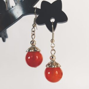 Oorbellen met een grote agaat kraal in de kleur oranje, met een gedecoreerd metalen kapje er bovenop.