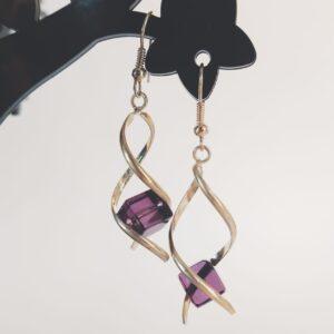 Oorbellen met een metalen wikkel met daartussen een vierkante glas kraal in de kleur paars.
