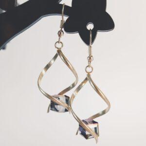 Oorbellen met een metalen helix gedecoreerd met streepjes met daartussen een vierkante glas kraal in de kleur paars en in facet geslepen.