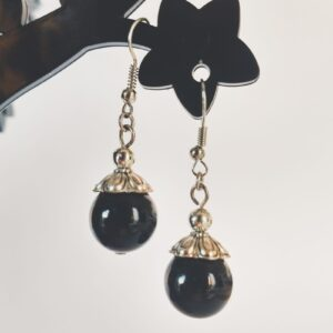 Oorbellen met een grote agaat kraal in de kleur zwart, met een gedecoreerd metalen kapje er bovenop.