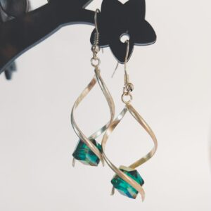 Oorbellen met een metalen wikkel met daartussen een vierkante glas kraal in de kleur groen en in facet geslepen.