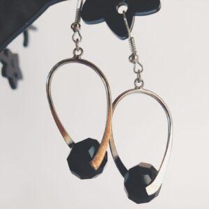 Oorbellen met een metalen helix met daartussen een glas kraal in de kleur zwart en geslepen in een briolette vorm.