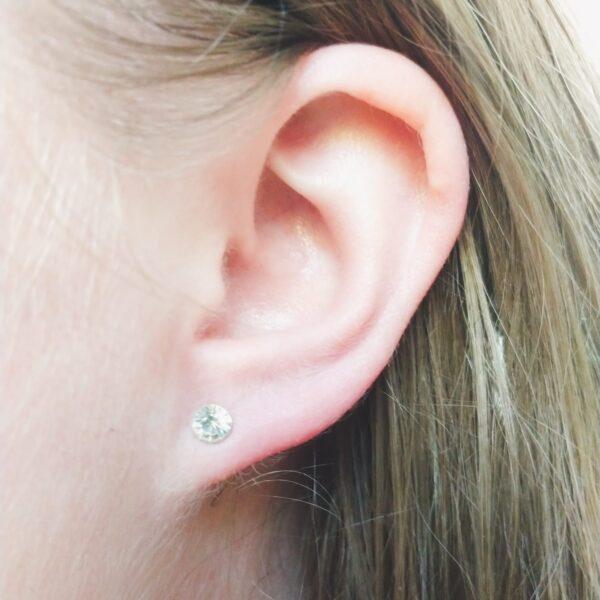 Oorstekers met strass steentjes in de kleur kristal. Op de foto is de oorsteker te zien in het oor van een blanke vrouw met blond haar.