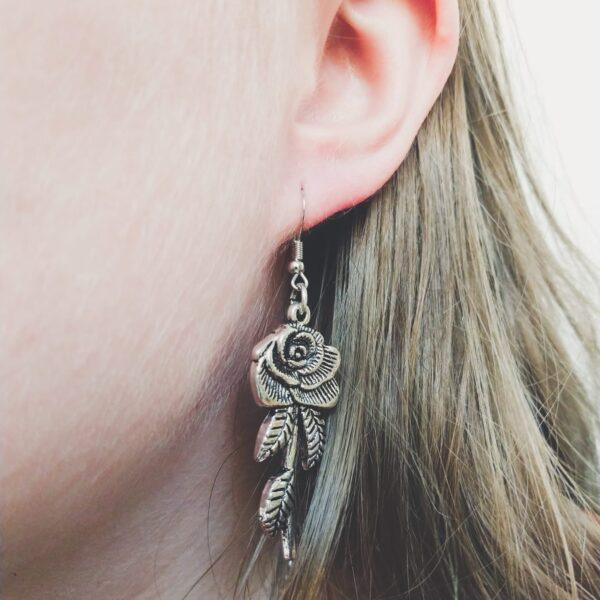 Oorbellen met een metalen hanger in de vorm van een roos. Op de foto is de oorbel te zien in het oor van een blanke vrouw met blond haar.