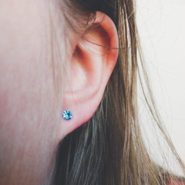 Oorstekers met kleine strass steentjes in de kleur licht blauw. Op de foto is de oorsteker te zien in het oor van een blanke vrouw met blond haar.