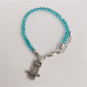 Armband swarovski xilion blue zirkon. Een armband met kleine 4 mm hoekige kraaltjes in blue zirkon (een blauw groene kleur). De armband wordt getoond om de pols van een blanke vrouw.