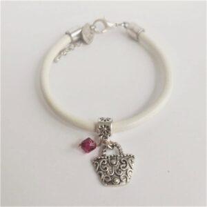 Armband wit leer swarovski donker roze. Wit leren armband met een metalen bedeltje in de vorm van een tasje met een swarovski kraal in de kleur fuchsia (donker roze).