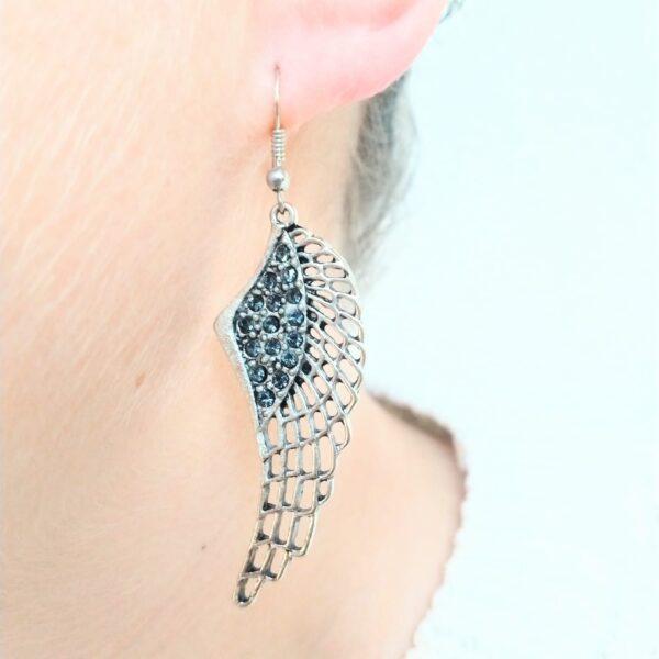 Oorbellen vleugel swarovski grijs. Oorbelen met een wing (vleugelvormige hanger) met swarovski steentjes in de kleur grijs. De oorbel wordt getoond in het oor van een blanke vrouw.