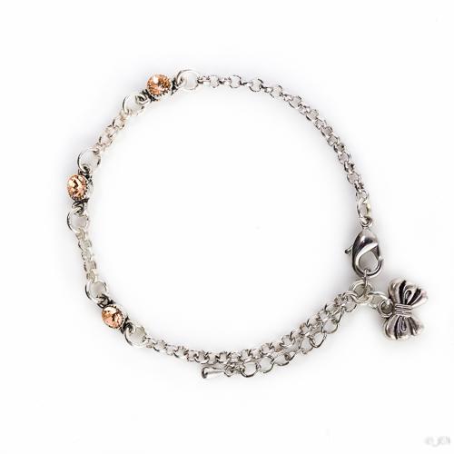 Fijne armband swarovski beige. Armband met kleine schakels van jasseron met 3 kleine swarovski steentjes in de kleur light peach, een beige kleur. Bij het slotje hangt een bedeltje in de vorm van een strikje.