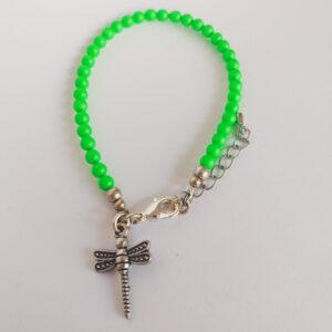 Armband swarovski parel neon groen. Een armband met kleine 4 mm swarovski pareltjes in een neon groene kleur. Bij het slotje hangt een bedeltje in de vorm van een libelle.