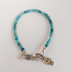 Armband natuursteen turquoise kiwi. Armband met 4 mm natuursteen turquoise kiwi kralen. Bij het slotje hangt een bedeltje in de vorm van een hand met een oog erop.