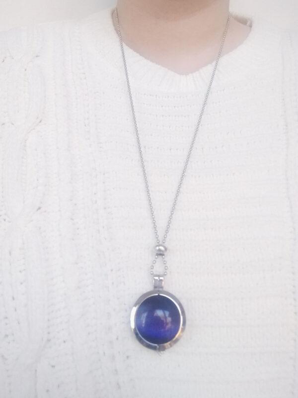 Ketting cateye blauw. Dubbelzijdige cateye steen in hanger aan een bolletjes ketting. De steen heeft 2 kanten, 1 met een cateye en 1 met kleine steentjes in een grijze/zwarte kleur. De ketting wordt getoond om de net van een blanke vrouw met een witte gebreide trui.