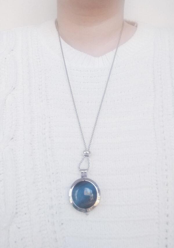 Ketting cateye grijs. Dubbelzijdige cateye steen in hanger aan een bolletjes ketting. De steen heeft 2 kanten, 1 met een cateye en 1 met kleine steentjes in een grijze/zwarte kleur. De ketting wordt getoond om de net van een blanke vrouw met een witte gebreide trui.